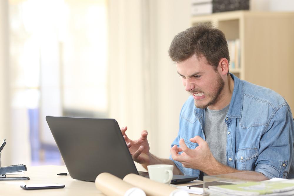 Mann ärgert sich am Laptop
